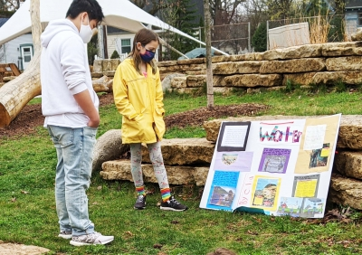 Two students standing outside looking at a project board about water.